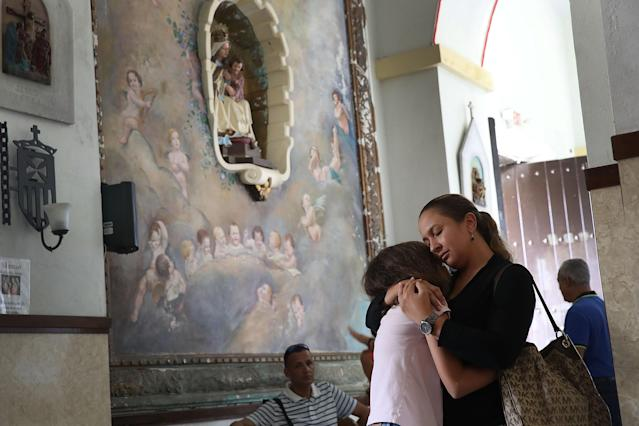 <p>Orisnela Solano hugs her daughter, Laura Goenaga as they attend a church service at the Parroquia Nuestra Senora de la Asuncion church September 24, 2017 in Aibonito, Puerto Rico. Puerto Rico experienced widespread damage after Hurricane Maria, a category 4 hurricane, passed through. (Photo: Joe Raedle/Getty Images) </p>