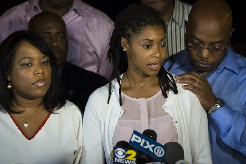Amy Carey, center, sister of Miriam Carey, speaks to the media outside the home of her sister Valarie, left, in the Bedford-Stuyvesant neighborhood of Brooklyn, Friday, Oct. 4, 2013, in New York. Law-enforcement authorities have identified Miriam Carey, 34, as the woman who, with a 1-year-old child in her car, led Secret Service and police on a harrowing chase in Washington from the White House past the Capitol Thursday, attempting to penetrate the security barriers at both national landmarks before she was shot to death, police said. The child survived. (AP Photo/John Minchillo)