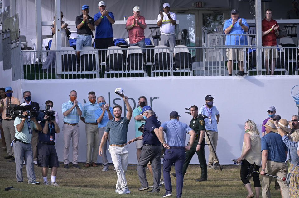 Sam Burns waves his hat to the crowd on the 18th green after winning the Valspar Championship golf tournament, Sunday, May 2, 2021, in Palm Harbor, Fla. (AP Photo/Phelan M. Ebenhack)