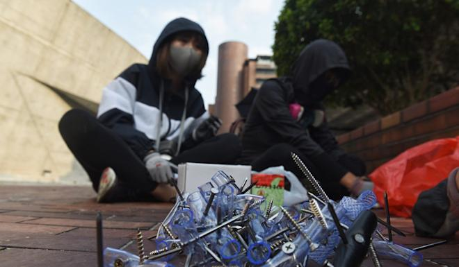 Protesters sit near barricades with supplies of nails to throw against the police at Hong Kong Polytechnic University on Thursday. Photo: EPA-EFE