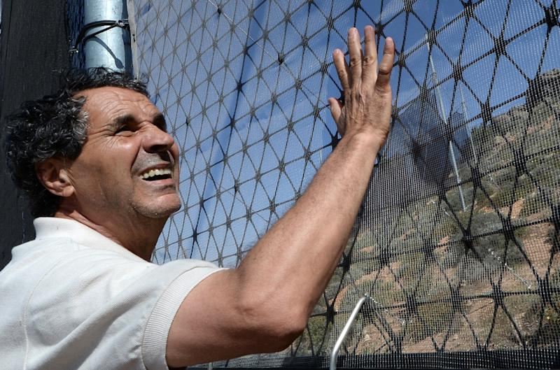 """Aissa Derhem, the president of the """"Dar Si Hamed for development, education and culture"""" association touches a fog fence in a hamlet on the outskirts of the southern coastal city of Sidi Ifni, on June 7, 2015 (AFP Photo/Fadel Senna)"""