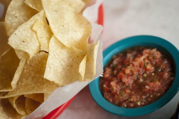 Red basket of tortilla chips next to a small blue bowl of salsa.