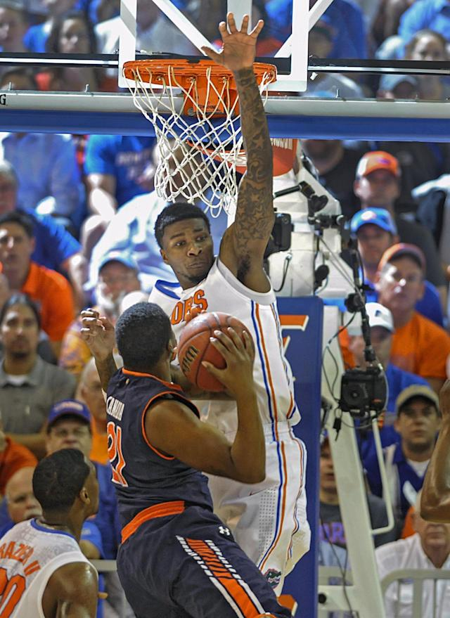 Florida's Chris Walker (23) goes high to block a shot by Auburn guard Malcolm Canada (21) during the first half of an NCAA college basketball game Wednesday Feb. 19, 2014 in Gainesville, Fla. Florida won the game 71-66. (AP Photo/Phil Sandlin)