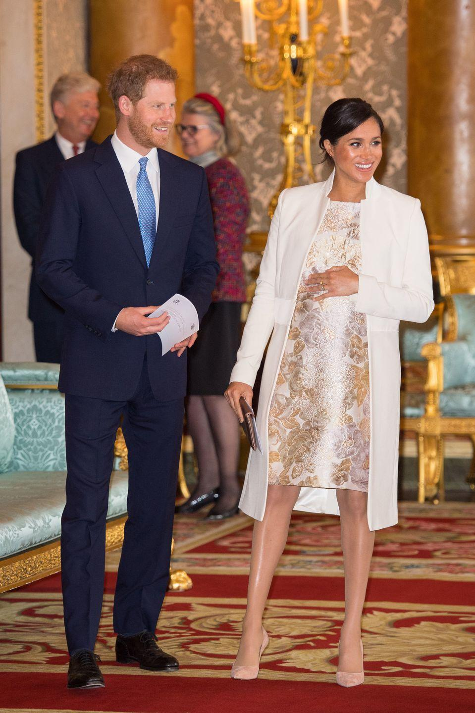 """<p>The Duchess of Sussex paired a metallic brocade dress with a rose gold clutch, nude Paul Andrew heels, and a recycled <a href=""""https://www.amandawakeley.com/us/cream-sculpted-tailoring-coat"""" rel=""""nofollow noopener"""" target=""""_blank"""" data-ylk=""""slk:Amanda Wakely cream coat"""" class=""""link rapid-noclick-resp"""">Amanda Wakely cream coat</a>, for Prince Charles's 50th Anniversary Investiture reception at Buckingham Palace. </p>"""