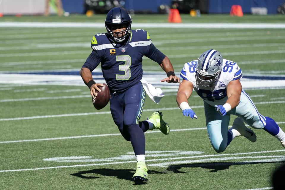 Russell Wilson scrambles with the ball trying to avoid a sack.