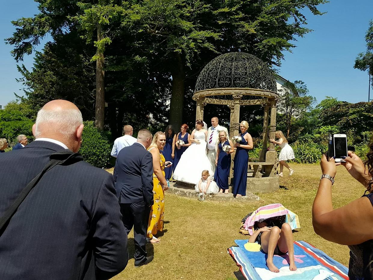 <em>Photobomb – Mark Ling and Mandy Cripwell say the stubborn sunbather refused to move as they tried to have their wedding pictures taken (Picture: SWNS)</em>