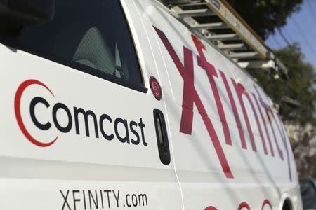 A Comcast sign is shown on the side of a vehicle in San Francisco, California in this file photo taken February 13, 2014. Comcast Corp, the largest U.S. cable operator, reported quarterly revenue that fell below analysts' estimates, mainly due to higher-than-expected video subscriber losses, July 22, 2014. REUTERS/Robert Galbraith/Files