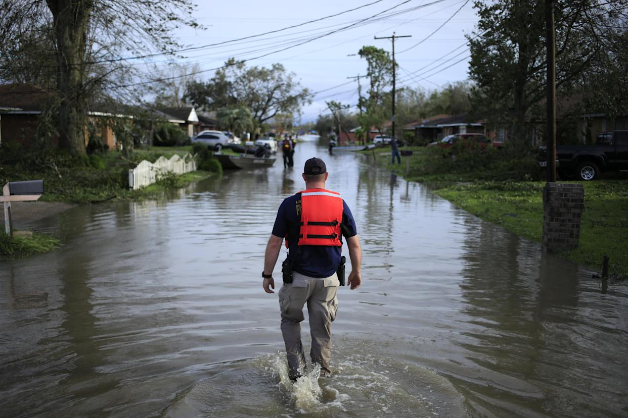 A first responder walks through floodwaters left by Hurricane Ida in LaPlace, La., on Aug. 30, 2021.