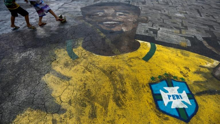 Children play football on a street painted with the image of Brazilian football player Gabriel Jesus in the neighborhood where he grew up in Sao Paulo, Brazil