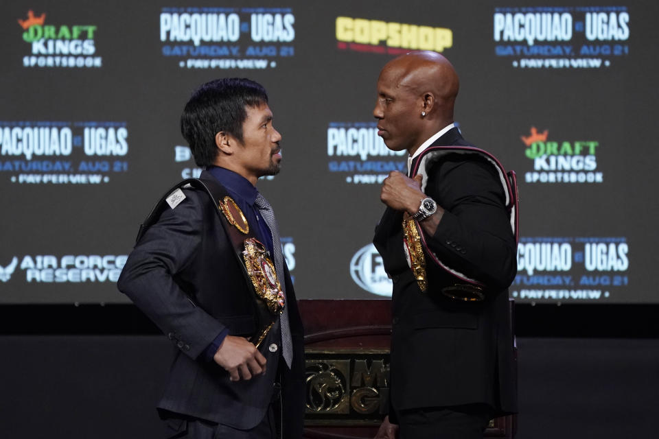 Manny Pacquiao, left, of the Philippines, and Yordenis Ugas, of Cuba, pose for photographers during a news conference Wednesday, Aug. 18, 2021, in Las Vegas. The two are scheduled to fight in a welterweight championship bout Saturday in Las Vegas. (AP Photo/John Locher)