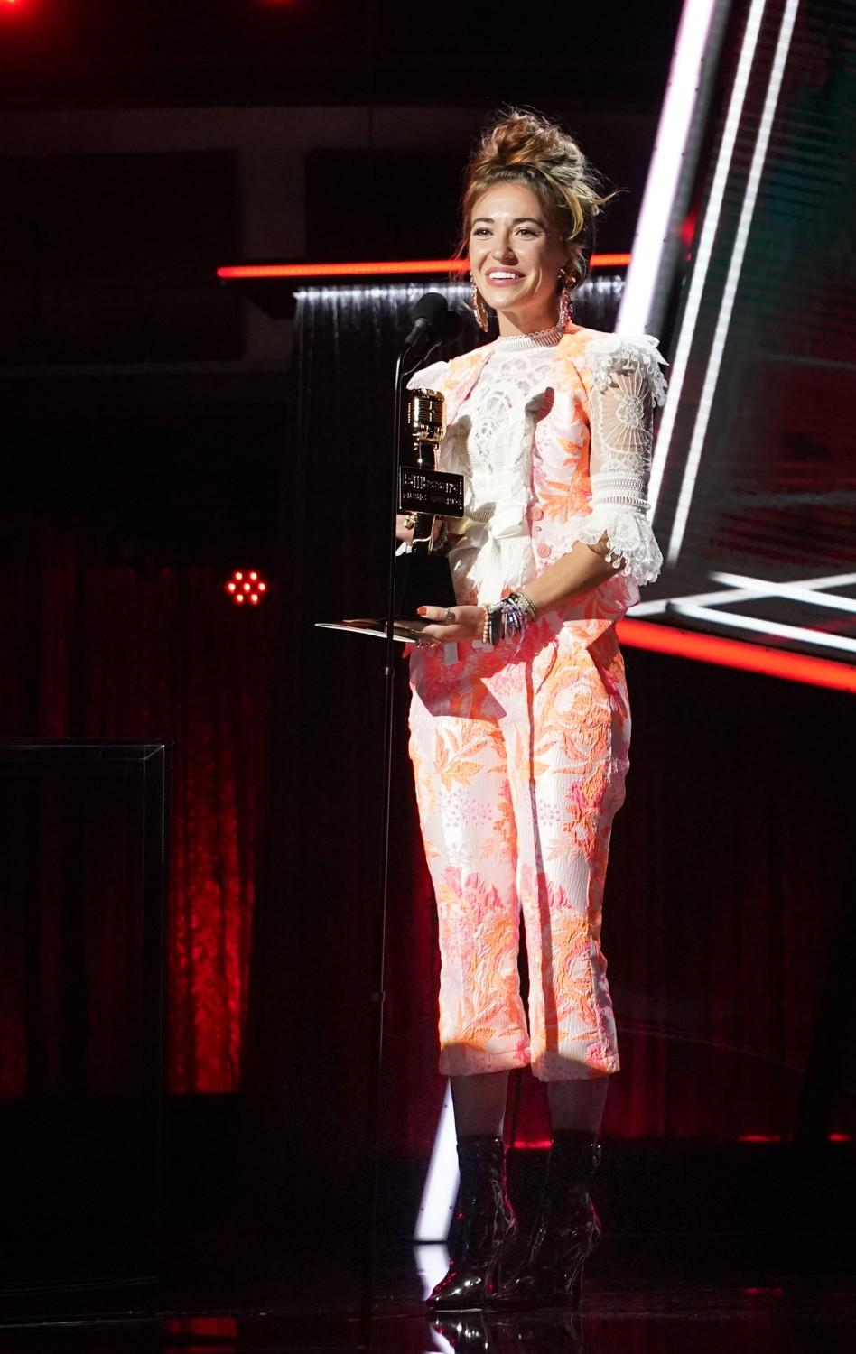 Lauren Daigle, in a lace and floral print pantsuit, holds her award.