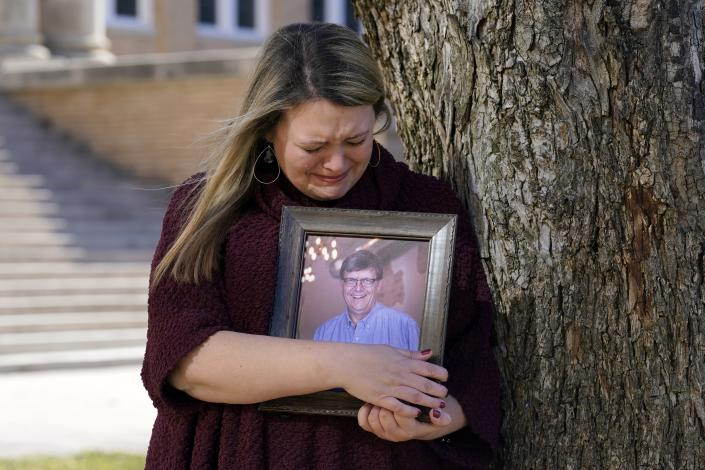 Katie Riggs Maxwell begins to cry as she hugs a portrait of her father Mark Riggs while posing for a photo, Wednesday, Dec. 16, 2020, on the campus of Abilene Christian University in Abilene, Texas. Mark Riggs, who was a professor at the school, passed away last Monday of COVID-19. (AP Photo/Tony Gutierrez)