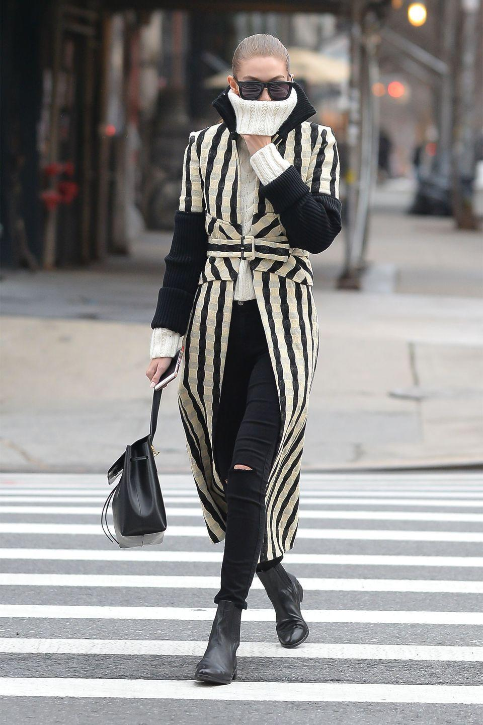 <p>Bundled up in a Victoria Beckham striped coat, white cable-knit sweater, black skinny jeans, black Chelsea boots, black sunglasses and a handbag while out in New York.</p>