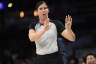 FILE - Referee Natalie Sago gestures during the first half of an NBA basketball game between the Washington Wizards and the Detroit Pistons in Washington, in this Monday, Nov. 4, 2019, file photo. With more female referees now in the NBA than ever before, it was only a matter of time before two women would be scheduled to work the same game. And Monday, Jan. 25, 2021, became that day. Natalie Sago and Jenna Schroeder made up two-thirds of the crew assigned to the Charlotte at Orlando game, the first time in NBA history that two women would be working a regular-season contest together. (AP Photo/Nick Wass)