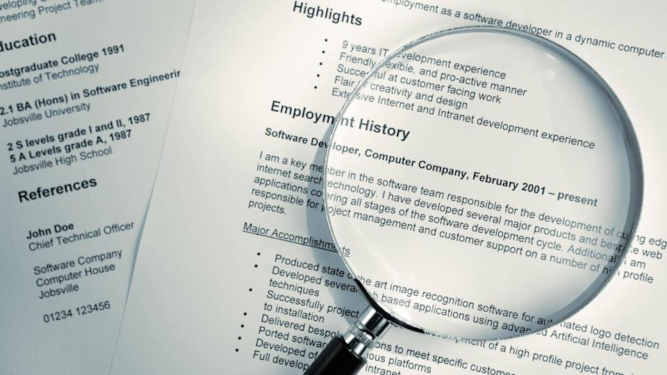 A blue tinted image of a magnifying glass lying on top of several sheets of a printout of resume documents.