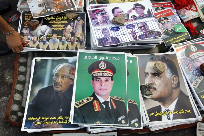 """FILE - In this Thursday, Aug. 8, 2013 file photo, posters showing Egyptian Army Chief Lt. Gen. Abdel-Fattah el-Sissi with Arabic that reads, """"Egypt over all,"""" center, are displayed between posters of late Presidents Anwar Sadat, left, and Gamal Abdel Nasser, right, in Tahrir Square in Cairo, Egypt. Arabic at right reads,"""" don't trust the Brotherhood"""" and at left, """" I was wrong when I released the Brotherhood out of prisons."""" The head of Egypt's military, Abdel-Fattah el-Sissi, is riding on a wave of popular fervor that is almost certain to carry him to election as president. Unknown only two years ago, a broad sector of Egyptians now hail him as the nation's savior after he ousted the Islamists from power, and the state-backed personality cult around him is so eclipsing, it may be difficult to find a candidate to oppose him if he runs. Still, if he becomes president, he faces the tough job of ruling a deeply divided nation that has already turned against two leaders.(AP Photo/Amr Nabil, File)"""