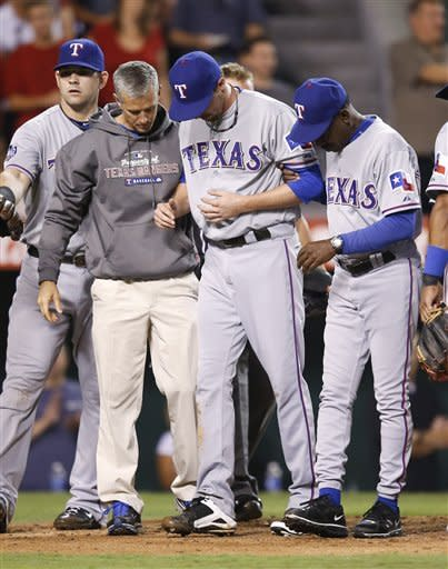 Texas Rangers relief pitcher Tanner Scheppers, center, is helped off the field by manager Ron Washington, right, and a trainer after he collided with Los Angeles Angels' Chris Iannetta in the fourth inning of a baseball game in Anaheim, Calif., Tuesday, Sept. 18, 2012. (AP Photo/Jae C. Hong)