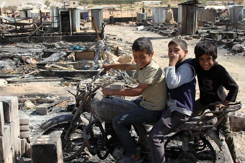 Syrian children sit on a damaged motorcycle at a former refugee camp that was burnt during clashes with jihadists in the eastern Lebanese town of Arsal, in August 2014 (AFP Photo/)