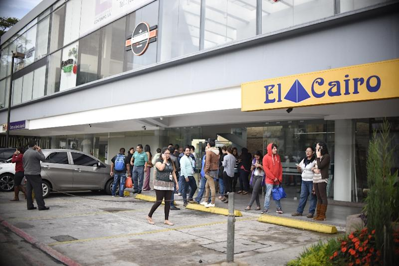 Office workers evacuate buildings in Guatemala City after a strong quake