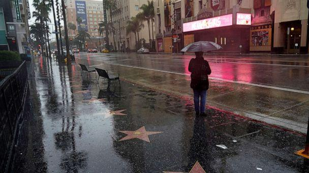 PHOTO: A woman waits at a bus stop in the rain on Dec. 28, 2020, in the Hollywood section of Los Angeles. (Marcio Jose Sanchez/AP)