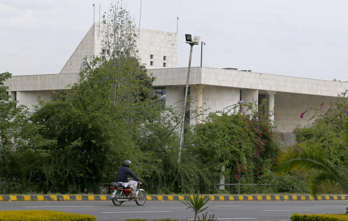 A motorcyclist rides past the French Embassy, in Islamabad, Pakistan, Thursday, April 15, 2021. The French embassy in Pakistan on Thursday advised all of its nationals and companies to temporarily leave the country after anti-France violence erupted in the Islamic nation over the arrest of a radical leader. Saad Rizvi was arrested Monday for threatening the government with mass protests if it did not expel French envoy Marc Baréty over the publication depictions of Islam's Prophet Muhammad. (AP Photo/Anjum Naveed)