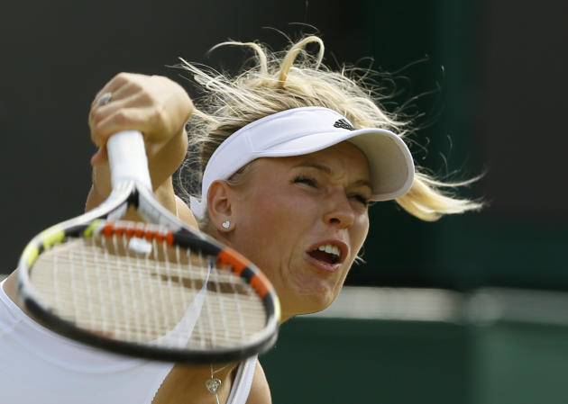 Caroline Wozniacki of Denmark returns a ball to Garbine Muguruza of Spain during their singles match at the All England Lawn Tennis Championships in Wimbledon, London, Monday July 6, 2015. (AP Photo/Kirsty Wigglesworth)