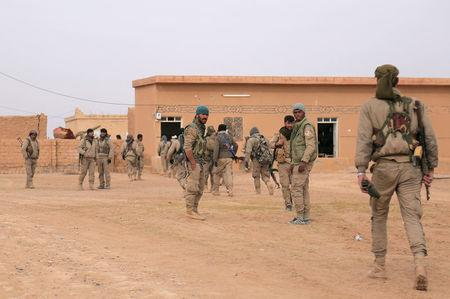 Syrian Democratic Forces (SDF) fighters walk with their weapons during an offensive against Islamic State militants in northern Raqqa province