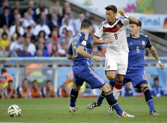 Germany's Mesut Ozil tries to get past his defenders Argentina's Martin Demichelis and Lucas Biglia (6) during the World Cup final soccer match between Germany and Argentina at the Maracana Stadium in Rio de Janeiro, Brazil, Sunday, July 13, 2014. (AP Photo/Felipe Dana)