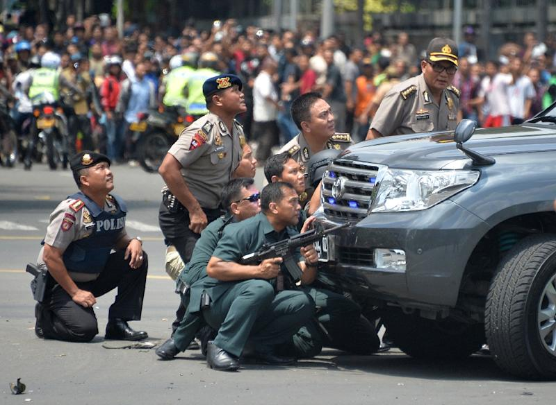 Indonesian police take position behind a vehicle as they pursue suspects after a series of blasts hit the Indonesia capital Jakarta on January 14 (AFP Photo/Bay Ismoyo)
