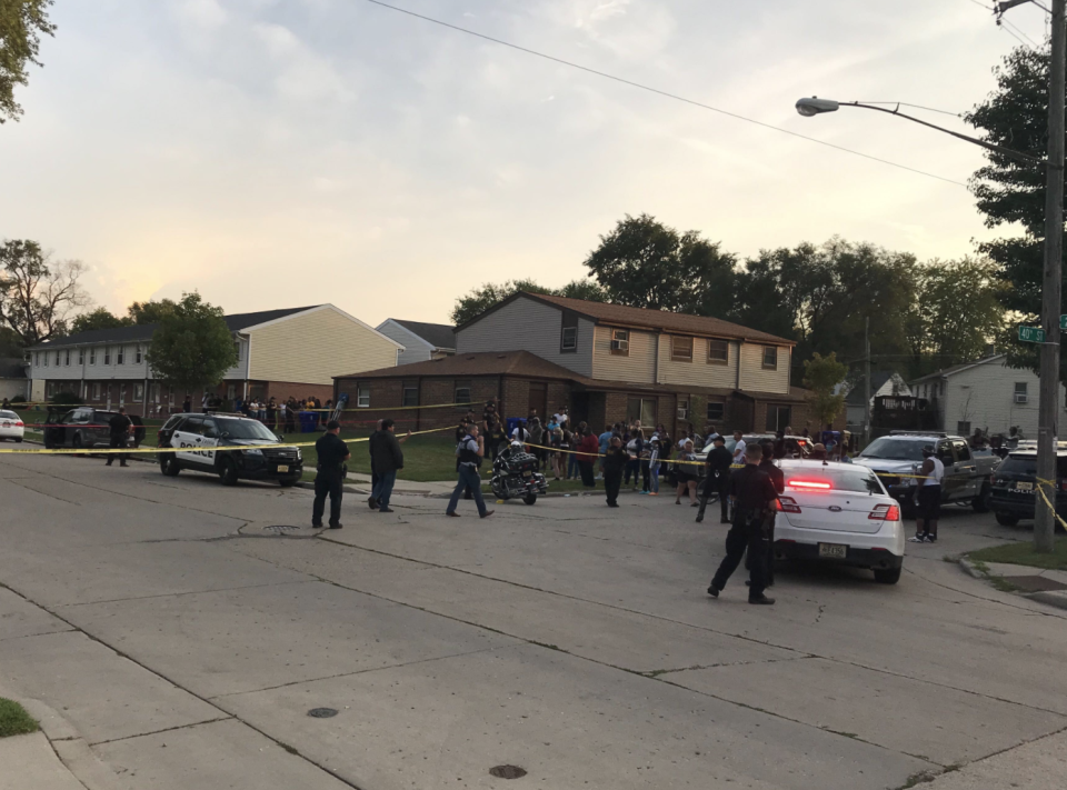 A large group of people can be seen gathering around police cars and tape.