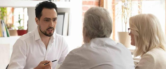 Young man faces older couple, sitting in office, discussing business
