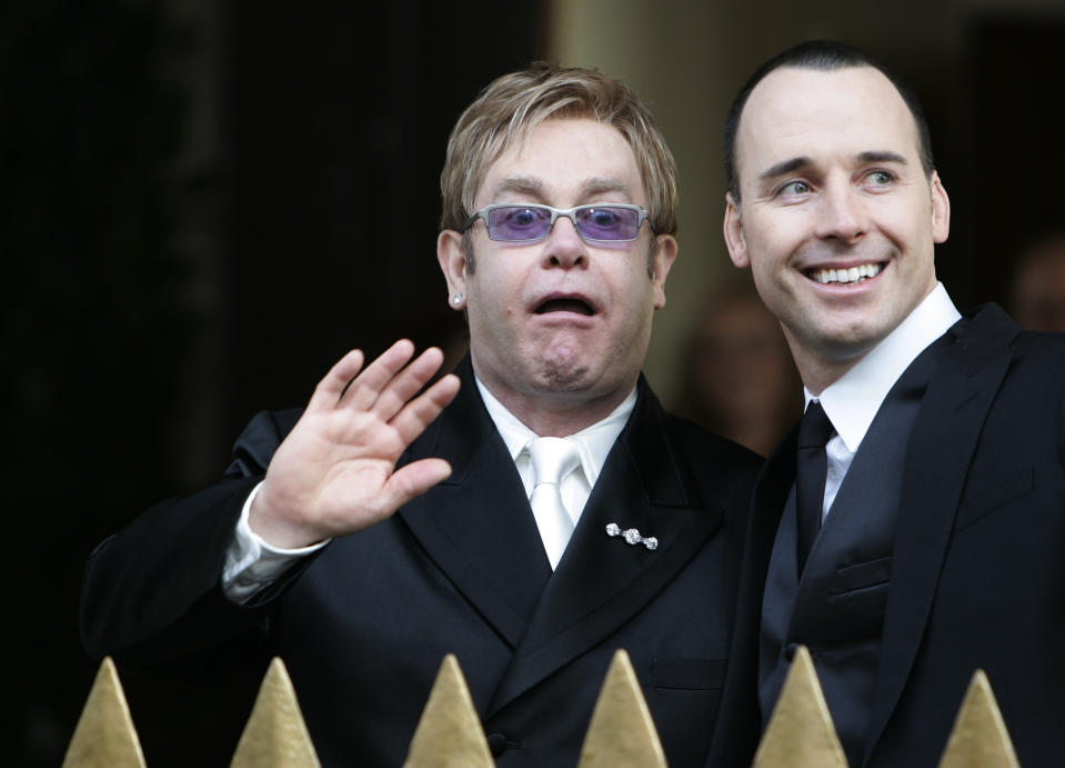 British pop star Elton John (L) and his partner David Furnish leave the Guildhall in Windsor, southern England, after their civil ceremony December 21, 2005. Elton John tied the knot with long-term partner David Furnish on Wednesday, joining hundreds of gay couples in England taking advantage of a new law to formalise their relationships. REUTERS/Kieran Doherty Pictures of the Month December 2005 Pictures of the Year 2005
