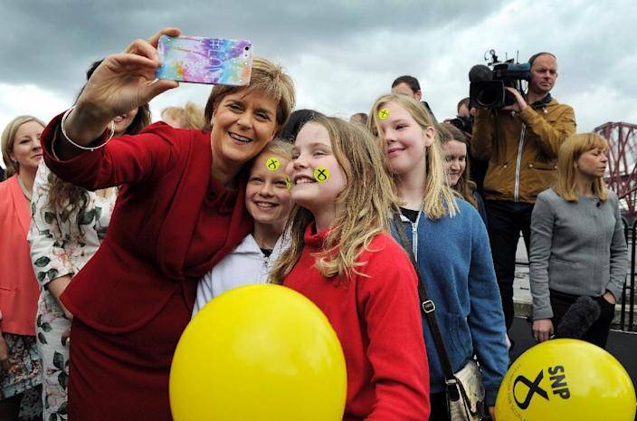 Scottish First Minister and Leader of the Scottish National Party Nicola Sturgeon takes a photo with local children in Queensferry, west of Edinburgh, on May 9, 2015 (AFP Photo/Andy Buchanan)