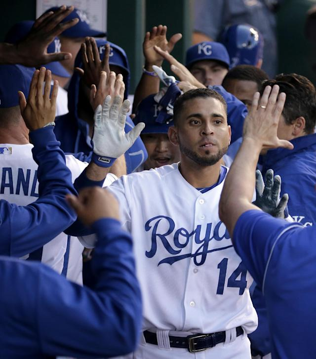 Kansas City Royals' Omar Infante celebrates in the dugout after Infante hit a two-run home run during the third inning of a baseball game against the Oakland Athletics Wednesday, Aug. 13, 2014, in Kansas City, Mo. (AP Photo/Charlie Riedel)