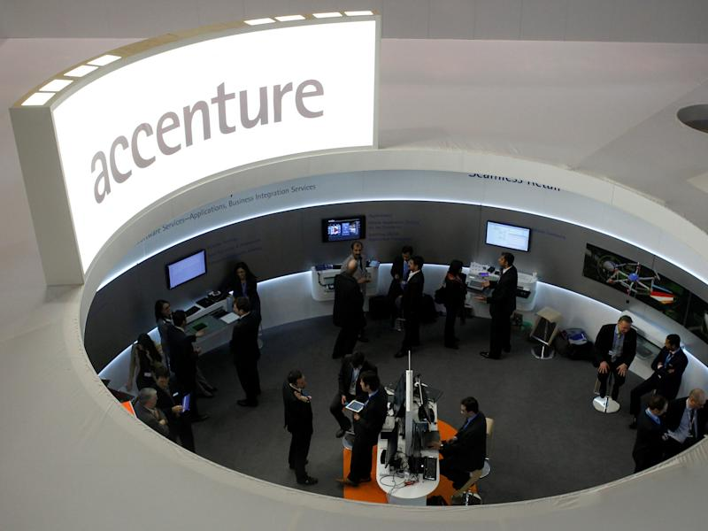 FILE PHOTO: Visitors look at devices at Accenture stand at the Mobile World Congress in Barcelona, February 26, 2013. REUTERS/Albert Gea
