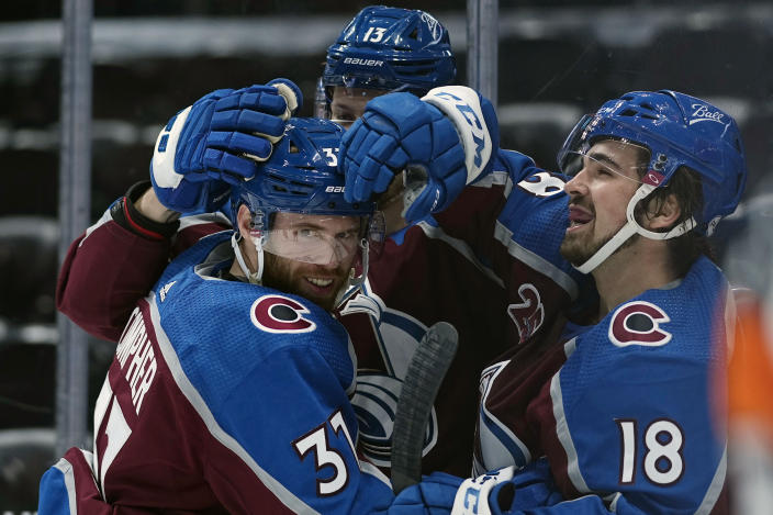 Colorado Avalanche left wing J.T. Compher (37) is congratulated by teammates Valeri Nichushkin (13) and Alex Newhook (18) after scoring a hat trick against the Los Angeles Kings during the second period of an NHL hockey game Wednesday, May, 12, 2021, in Denver. (AP Photo/Jack Dempsey)