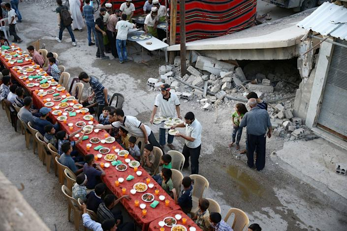 People gather for Iftar (breaking fast), organised by Adaleh Foundation, amidst damaged buildings during the holy month of Ramadan in the rebel held besieged Douma neighbourhood of Damascus, Syria, June 18, 2017. Picture taken June 18, 2017. REUTERS/Bassam Khabieh TPX IMAGES OF THE DAY