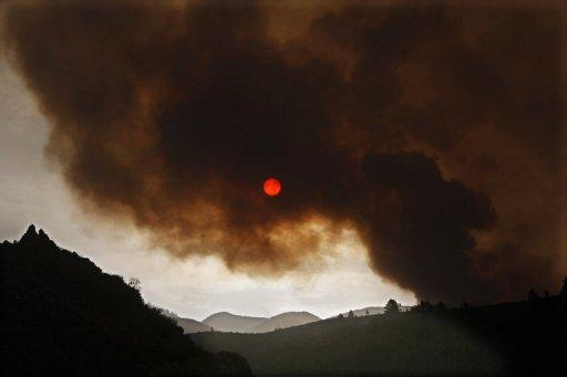 Dark clouds of smoke billow from a wildfire over the town of Tijoco Bajo, on the Spanish Canary Island of Tenerife. Spanish authorities evacuated the town of Vilaflor on the Canary Islands Tuesday as a raging wildfire reached it, an AFP photographer witnessed