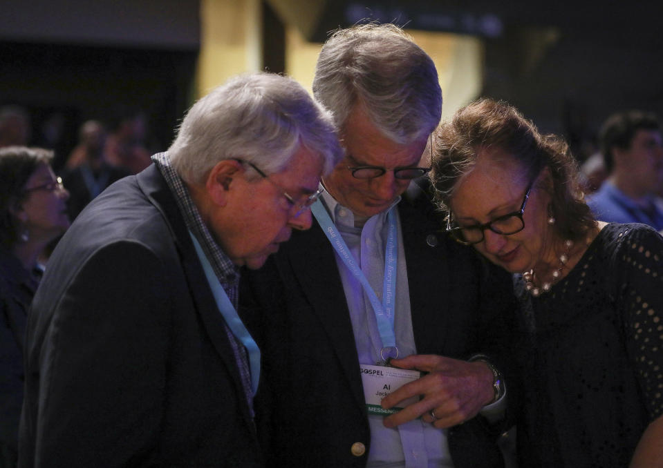 """FILE - In this Wednesday, June 12, 2019 file photo, from left, Dick Lane, Al Jackson and his wife, Kem Jackson, pray on the second day of the Southern Baptist Convention's annual meeting in Birmingham, Ala. """"The reason we're here is because we trust Jesus,"""" his wife Kem Jackson said. As Southern Baptists prepare for their biggest annual meeting in more than a quarter-century in June 2021, accusations that leaders have shielded churches from claims of sexual abuse and simmering tensions around race threaten to once again mire the nation's largest Protestant denomination in a conflict that can look more political than theological. ( Jon Shapley/Houston Chronicle via AP, File)"""