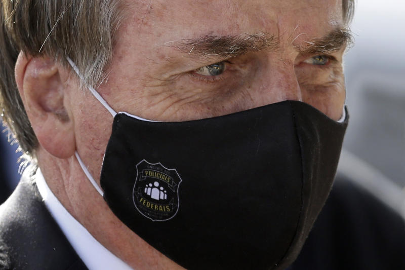 Brazil's President Jair Bolsonaro, wearing a face mask amid the new coronavirus pandemic, faces supporters as he leaves his official residence of Alvorada palace in Brasilia, Brazil, Tuesday, May 26, 2020. (AP Photo/Eraldo Peres)