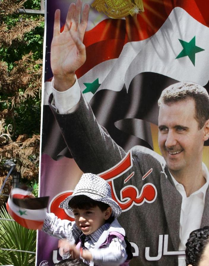 A Syrian child waves his national flag in front of a poster of Syrian President Bashar al-Assad in Damascus, following the re-opening ceremony of the rail route between two neighbourhoods in the Syrian capital, Raboeh and Dumar, on May 1, 2015 (AFP Photo/Louai Beshara)
