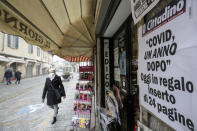 "A woman walks past a newsstand with the local paper headline reading ""Covid, One Year After"", in Codogno, northern Italy, Sunday, Feb. 21, 2021. The first case of locally spread COVID-19 in Europe was found in the small town of Codogno, Italy one year ago on February 21st, 2020. The next day the area became a red zone, locked down and cutoff from the rest of Italy with soldiers standing at roadblocks keeping anyone from entering of leaving. (AP Photo/Luca Bruno)"