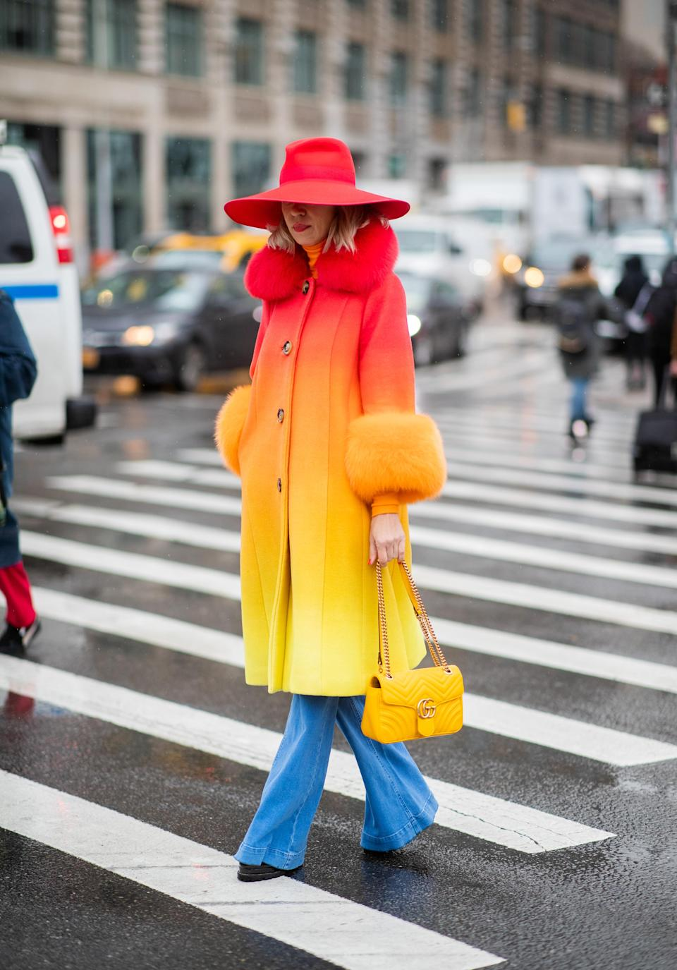 <p>A guest wearing an ombre coat, red hat and blue trousers during New York Fashion Week. <em>[Photo: Getty]</em> </p>