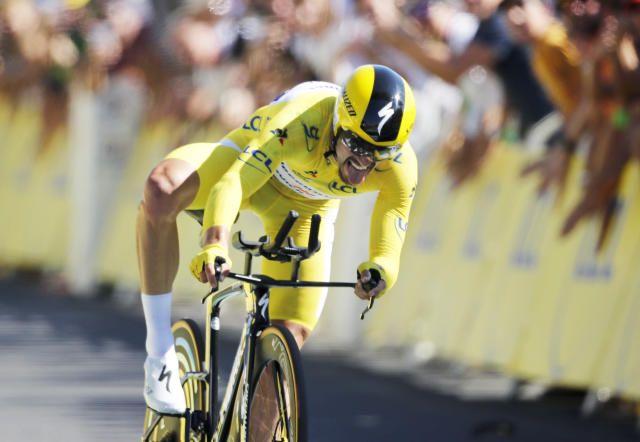 France's Julian Alaphilippe wearing the overall leader's yellow jersey crosses the finish line to win the thirteenth stage of the Tour de France cycling race, an individual time trial over 27.2 kilometers (16.9 miles) with start and finish in Pau, France, Friday, July 19, 2019. (AP Photo/Christophe Ena)