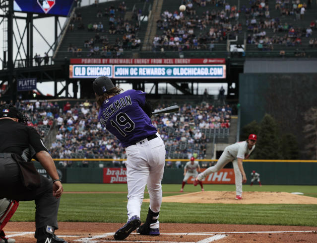 Colorado Rockies' Charlie Blackmon (19) hits a home run off Philadelphia Phillies starting pitcher Aaron Nola, back right, in the first inning of a baseball game in Denver, Saturday, April 20, 2019. (AP Photo/Joe Mahoney)