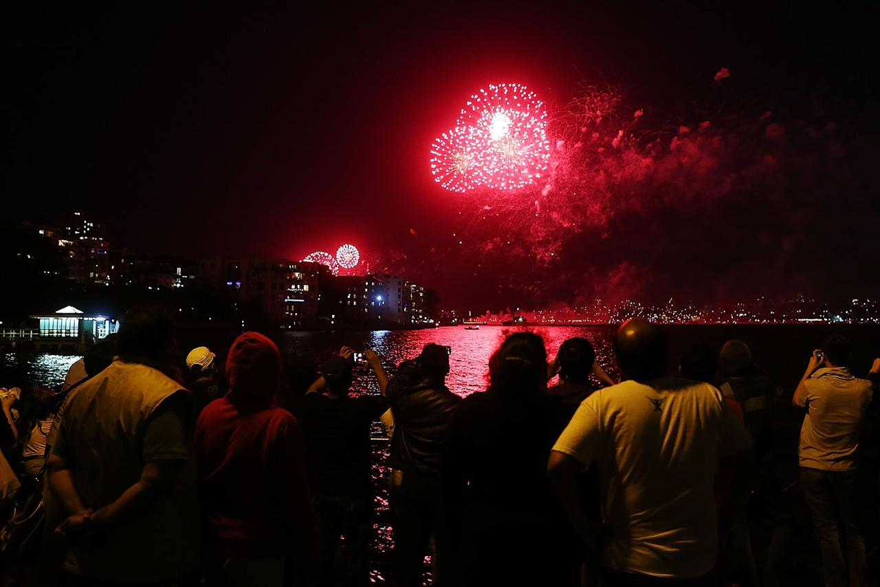 SYDNEY, AUSTRALIA - DECEMBER 31:  People watch fireworks around the harbour during New Years Eve celebrations on Sydney Harbour on December 31, 2012 in Sydney, Australia.  (Photo by Brendon Thorne/Getty Images)