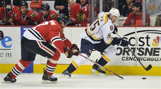 Chicago Blackhawks' Brent Seabrook, left, and Nashville Predators' Craig Smith (15) fight for the puck during the first period of an NHL hockey game Friday, April 19, 2013, in Chicago. (AP Photo/Jim Prisching)