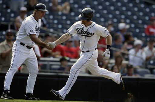San Diego Padres' Logan Forsythe, right, is greeted by third base coach Glenn Hoffman while rounding third after hitting a home run against the St. Louis Cardinals during the second inning of their baseball game on Wednesday, Sept. 12, 2012, in San Diego. (AP Photo/Gregory Bull)