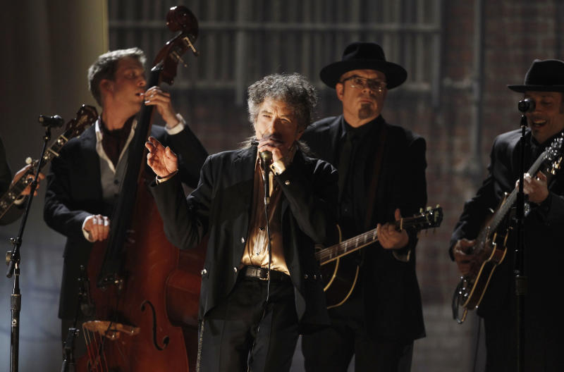 """FILE - In this Feb. 13, 2011, file photo, Bob Dylan, center, performs at the 53rd annual Grammy Awards in Los Angeles. Dylan won the 2016 Nobel Prize in literature on Thursday, Oct. 13, 2016, a stunning announcement that for the first time bestowed the prestigious award on a musician for """"having created new poetic expressions within the great American song tradition."""" (AP Photo/Matt Sayles, File)"""