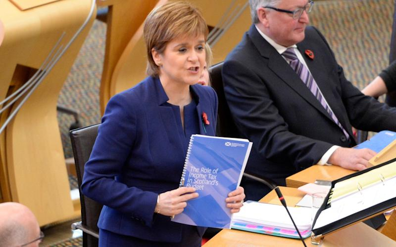 Nicola Sturgeon holds up a newly-published Scottish Government paper on taxation during First Minister's Questions in the Scottish Parliament - Corbis News